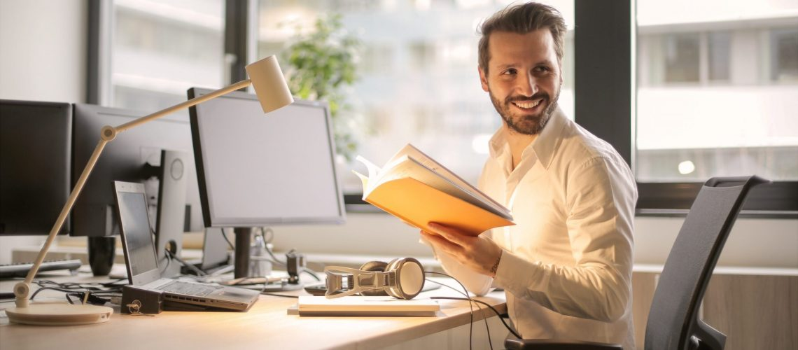 photo-of-man-holding-a-book-927022